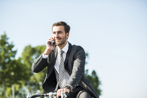 Young businessman riding bicycle, talking on the phone - UUF005576