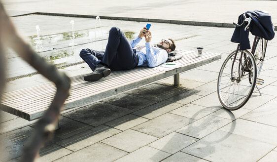 Young businessman lying on bench, working - UUF005590