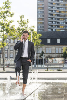 Young businessman standing in fountain, talking on the phone - UUF005591