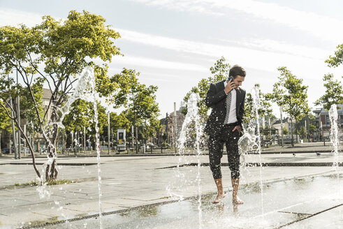 Young businessman standing in fountain, talking on the phone - UUF005592