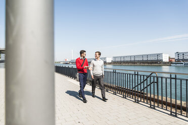 Two young businessmen walking by the riverside - UUF005623