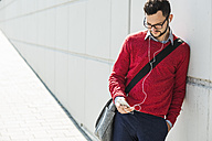 Young businessman using smart phone, wearing ear phones - UUF005627