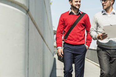 Two young businessmen walking in city carrying files - UUF005630