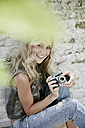 Portrait of smiling blond woman with an old camera - FMKF002064