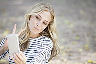 Portrait of smiling blond woman taking a selfie with her smartphone - FMKF001995