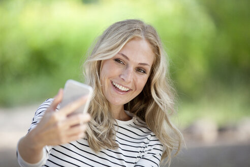 Portrait of happy blond woman taking a selfie with her smartphone - FMKF001996