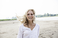 Portrait of smiling blond woman with blowing hait on a beach - FMKF001998