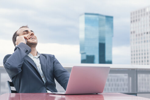 Happy businessman, laughing, Laptop on table - BZF000221