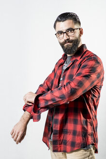Portrait of hipster rolling up sleeve of his shirt - JASF000012