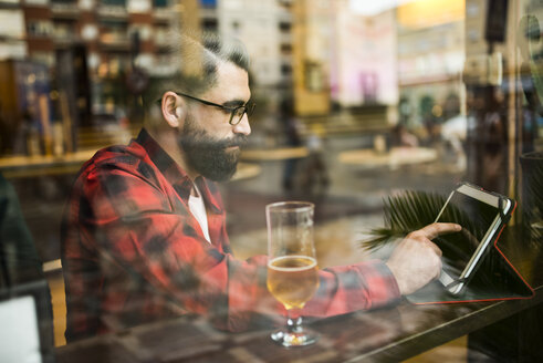 Adult bearded hipster style man touching tablet in bar and drinking alchohol near to window - JASF000019