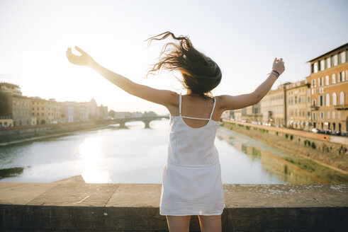 Italy, Florence, back view of happy woman wearing white summer dress standing on a bridge at sunset - GEMF000325