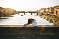 Italy, Florence, woman wearing white summer dress relaxing on a bridge at sunset - GEMF000331
