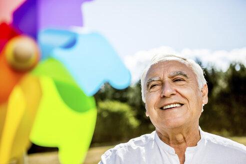Smiling senior man with pinwheel outdoors - RKNF000177