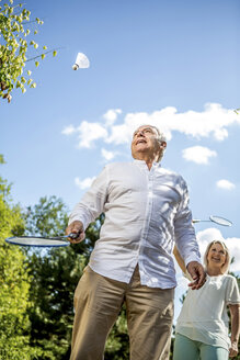 Happy elderly couple playing badminton outdoors - RKNF000189