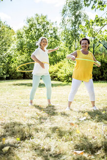 Happy mature women practising with hula hoops on meadow - RKNF000193