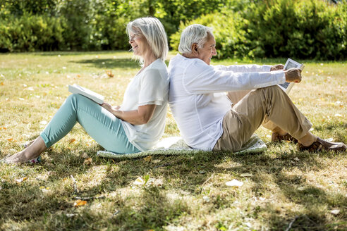 Elderly couple sitting back to back in grass reading books - RKNF000200