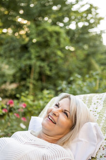 Smiling mature woman relaxing in garden - RKNF000208