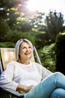 Mature woman relaxing in deckchair in garden - RKNF000222