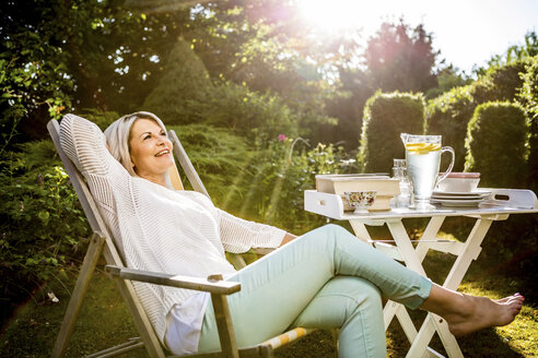 Mature woman relaxing in deckchair in garden - RKNF000225
