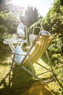 Mature woman relaxing in deckchair in garden with man in background - RKNF000227