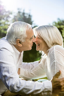 Happy elderly couple kissing outdoors - RKNF000358