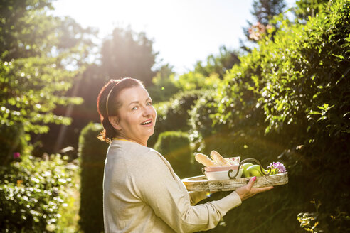 Mature woman carrying tray in garden - RKNF000244