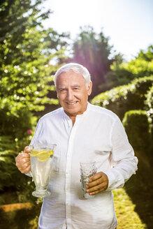 Smiling senior man holding carafe of water in garden - RKNF000245