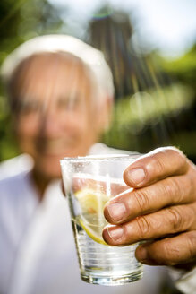 Close-up of senior man holding glass of water - RKNF000247