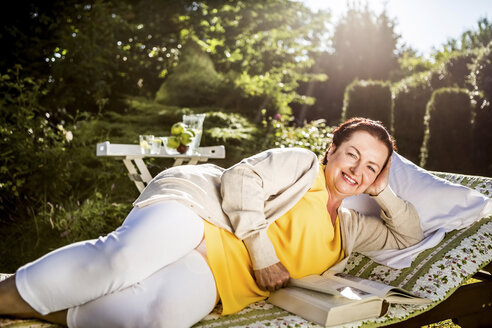 Smiling mature woman reading book on garden lounge - RKNF000253