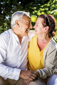 Happy elderly couple in garden balancing apple between their heads - RKNF000268