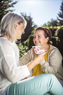 Happy mature women in garden with coffee cups - RKNF000270
