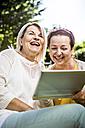 Happy mature women in garden with digital tablet - RKNF000272