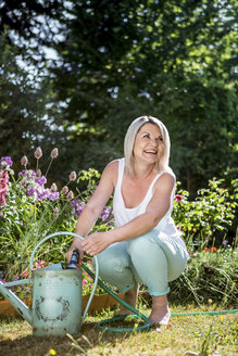 Smiling mature woman with hose and watering can in garden - RKNF000295