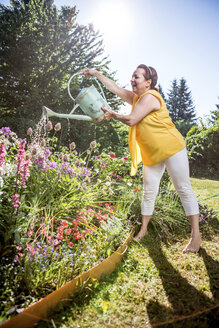 Smiling mature woman watering flowers in garden - RKNF000298