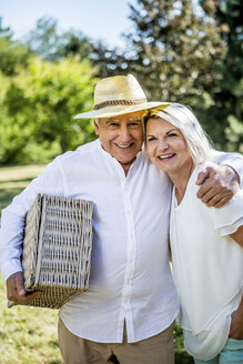 Portrait of smiling elderly couple with picnic basket - RKNF000332
