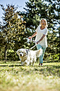 Mature woman with dog on a meadow - RKNF000371