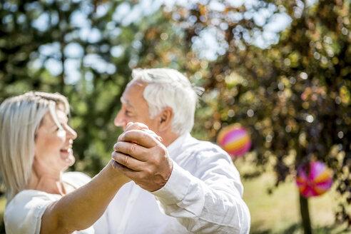 Happy elderly couple dancing outdoors - RKNF000347