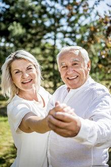 Happy elderly couple dancing outdoors - RKNF000352