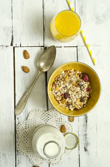 Bowl of fruit muesli, glass of mango smoothie, spoon and bottle of milk - ODF001239