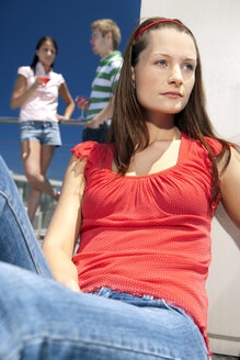 Young woman in sunshine looking away - TOYF001385