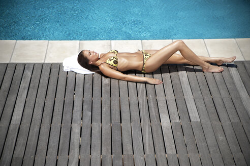 Young woman sunbathing at the poolside - TOYF001338
