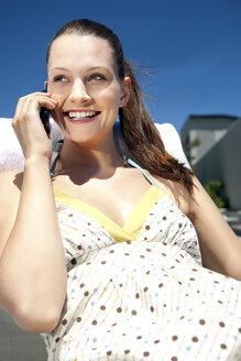 Happy young woman on cell phone under blue sky - TOYF001340