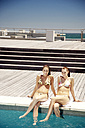 Two happy young women sitting at the poolside - TOYF001386