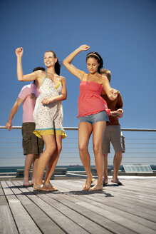 Happy friends dancing on wooden terrace - TOYF001345