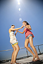 Two happy friends dancing on wooden terrace - TOYF001346