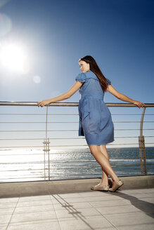 Young woman leaning on railing by the sea - TOYF001393