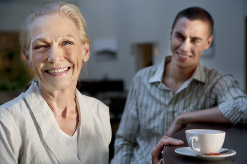 Portrait of smiling senior woman with cup of coffee and young man in background - TOYF001377