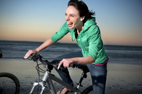 Carefree young woman on mountainbike on the beach - TOYF001397