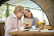 Smiling senior couple with digital tablet having breakfast in a cafe - TOYF001266