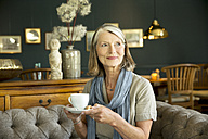 Smiling senior woman in lounge room with cup of coffee - TOYF001268